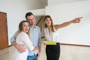 Real estate agent showing a house to a happy couple and smiling while talking